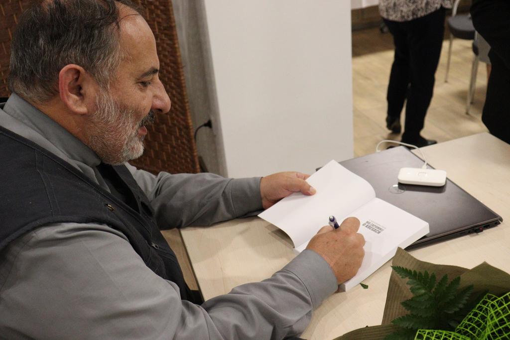 Zdjęcie przedstawia ks. Tadeusza Isakowicza-Zaleskiego podpisującego książki podczas Bialskiej Akademii Wiedzy