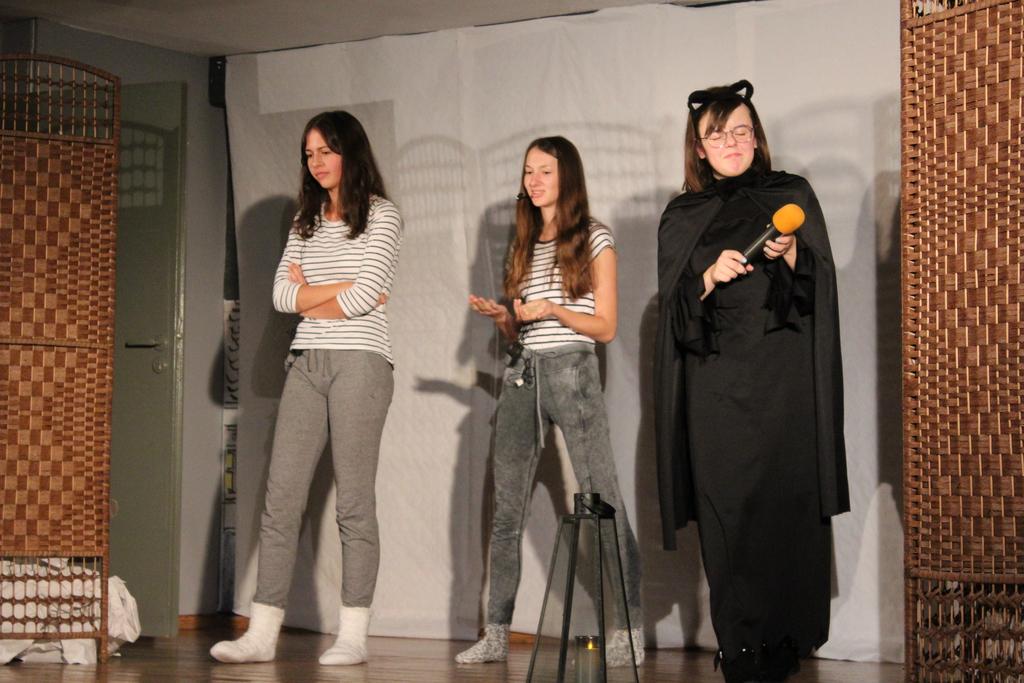 Zdjęcie przedstawia trzy aktorki z grupy teatralnej podczas spektaklu.