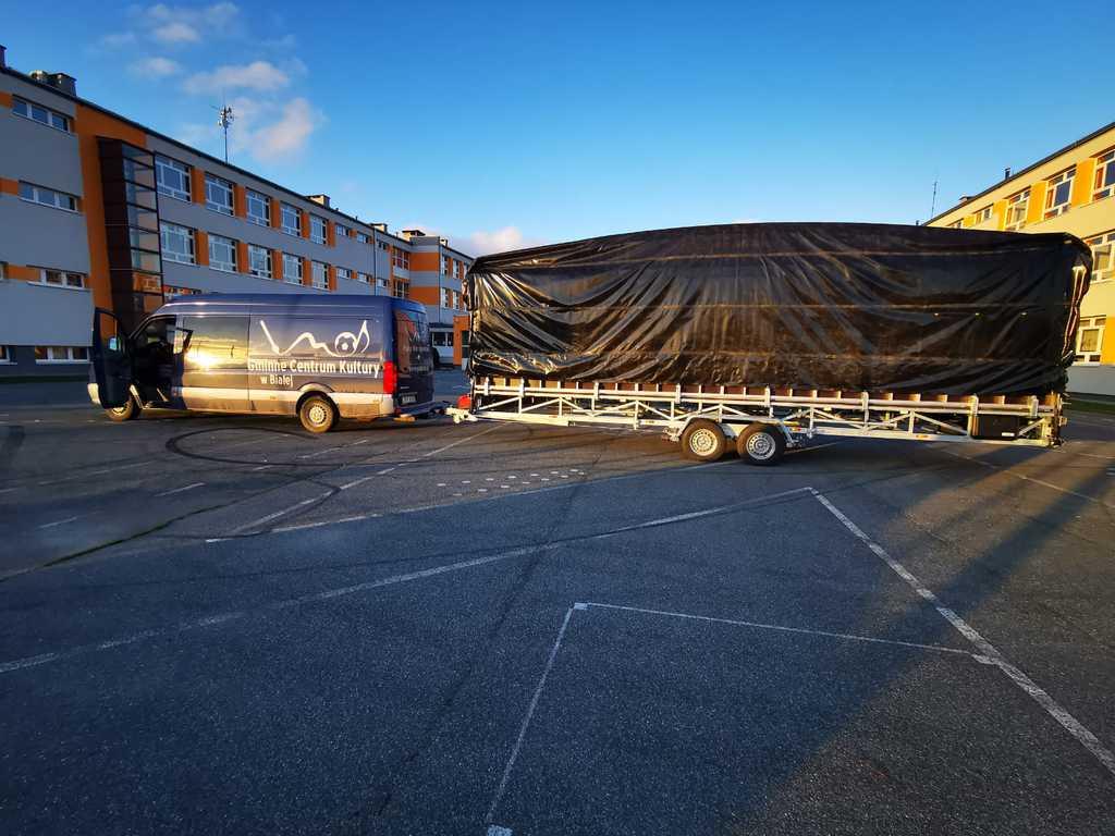Zdjęcie przedstawia mobilną scenę złożoną i zaczepioną do samochodu Gminnego Centrum Kultury w Białej