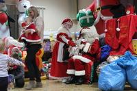 Zdjęcie przedstawia św. Mikołaja oraz jego pomocnicę i uczestników mikołajek podczas rozdawania prezentów
