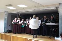 Zdjęcie przedstawia chór ZGODA podczas występu na scenie w sali w GCK w Białej