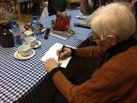 Zdjęcie przedstawia Annę Myszyńską podczas podpisywania książki