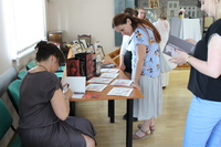 Zdjęcie przedstawia autorkę obrazów w trakcie podpisywania książki oraz uczestników spotkania.
