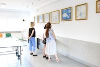 Zdjęcie przedstawia uczestników spotkania podczas oglądania wystawy.