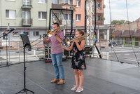 Zdjęcie przedstawia instruktora nauki gry na instrumentach dętych oraz jego uczennicę na scenie.