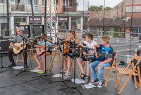 Zdjęcie przedstawia grupę gitarzystów oraz instruktora na scenie.