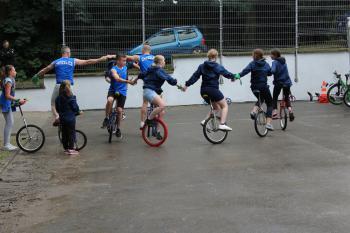 Zdjęcie przedstawia monocyklistów podczas pokazu w parku w Białej