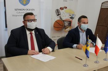 Zdjęcie przedstawia podpisanie umowy na remont wieży prudnickiej przez Dyrektora Gminnego Centrum Kultury w Białej oraz Członka Zarządu Województwa Opolskiego