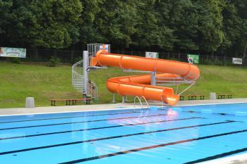 Zdjęcie przedstawia część basenu wraz z jedno torową zjeżdżalnią