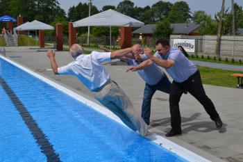 Zdjęcie przedstawia otwarcie basenu i wrzucenie do wody ówczesnego Burmistrza Białej Arnolda Hinderę