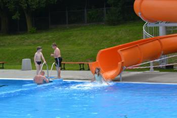 Zdjęcie przedstawia osoby korzystające z basenu i zjeżdżalni basenowej