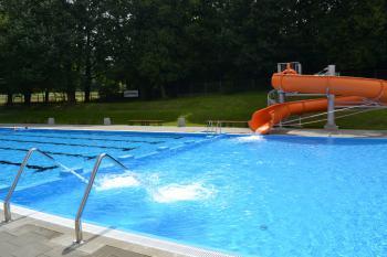 Zdjęcie przedstawia widok na część płytką basenu wraz z biczami wodnymi i zjeżdżalnią