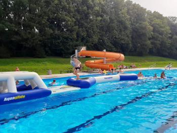 Zdjęcie przedstawia dzieci bawiące się na wodnym torze przeszkód na basenie w Białej
