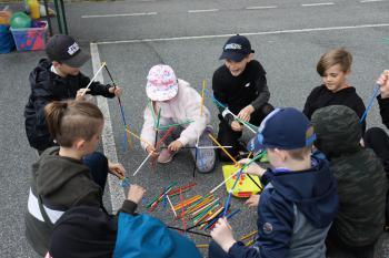 Na zdjęciu dzieci układające konstrukcję z kolorowych patyczków