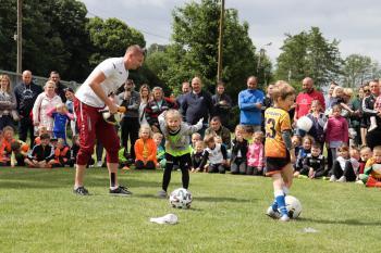 Zdjęcie przedstawia Dawida Krzyżowskiego podczas pokazu trików piłkarskich wśród dzieci