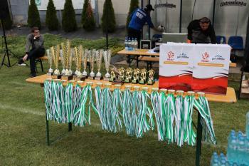 Zdjęcie przedstawia medale, puchary i nagrody dla zawodników