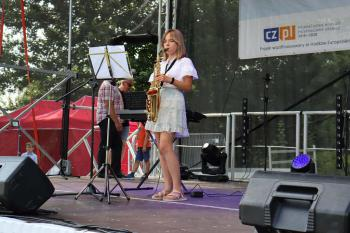 Zdjęcie przedstawia uczestniczkę imprezy grającą na saksofonie